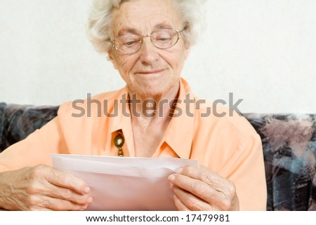 a elderly woman is opening a envelope, focus on the envelope for your own text - stock photo