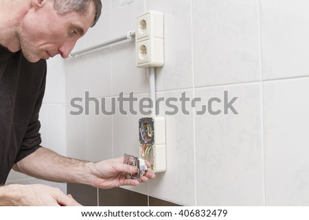 A electrician with a screwdriver in his hand during the installation of external electrical outlets.