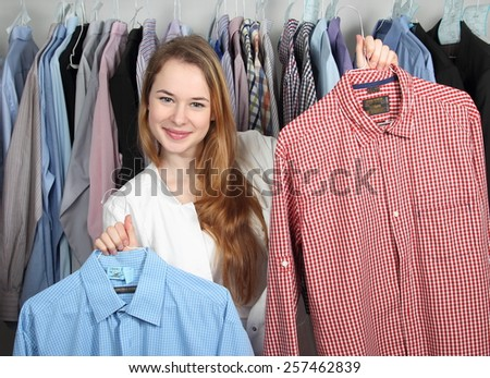 A Employee of a dry cleaning presenting two clean shirts - stock photo