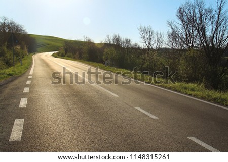 A empty road in the hilly countryside of Tuscany, Italy.