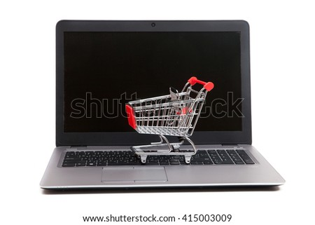 A empty shopping cart is standing on keyboard of notebook