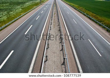 A empty stretch of a brand new two lane highway - stock photo