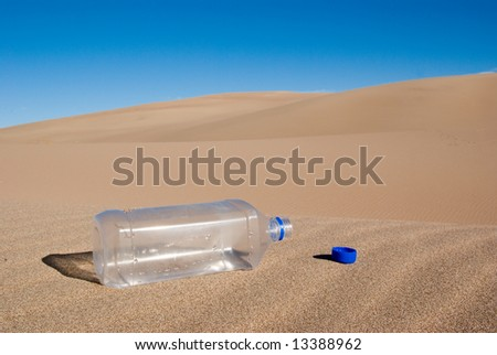 A empty water bottle in the middle of the desert