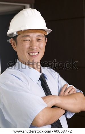 A engineer with a helmet, working in office - stock photo