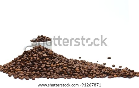 A espresso cup buried with dark roasted coffee beans, on a coffee mountain with limited depth of field (shallow depth of field), isolated on white.