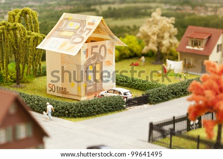 a euro bill house in a green neighborhood scenery - stock photo