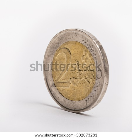 A 2 euro coin standing upright on a white background
