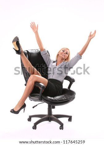 A excited business woman sitting in a swivel chair with her legs and hands up in the air isolated on white in the vertical format.