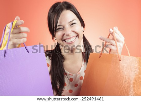 A excited woman with tree shopping bag on his hand. - stock photo