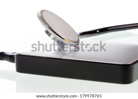 A external harddisk is monitored by a stethoscope. - stock photo