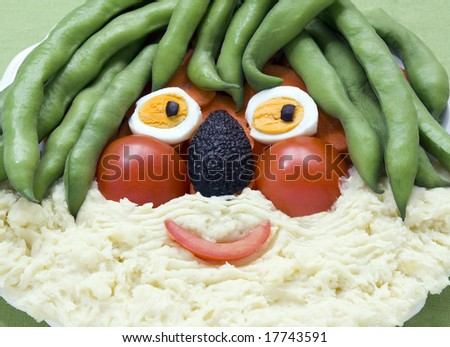 A face made of food for kids fun. Broad beans, tomato, eggs, avocado, carrots and mashed potatoes. All in focus - stock photo
