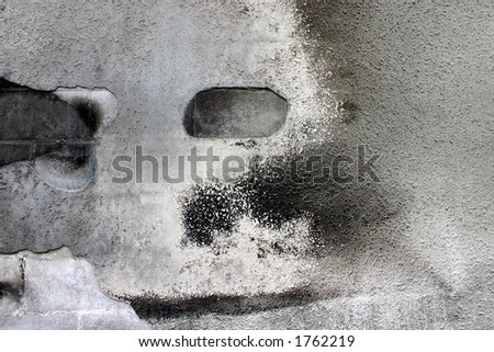 A face seems to appear on a weathered stucco wall