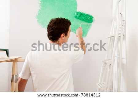 A faceless male painting a wall with a roller brush, home improvements