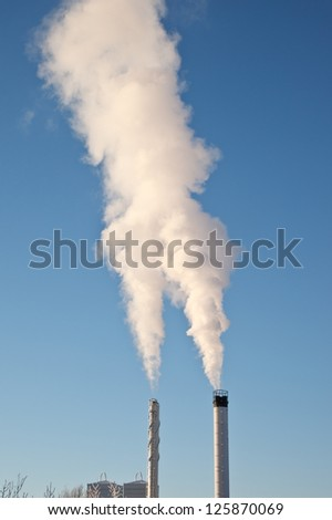 A factory chimney with rising smoke against a blue sky