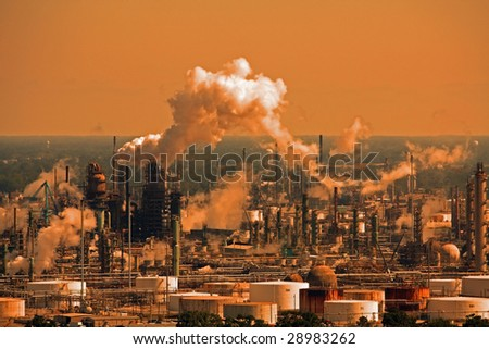 A factory plant emitting smoke into the atmosphere. - stock photo