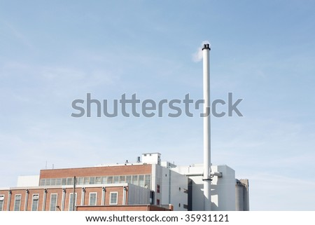 A factory with a tall chimney - stock photo