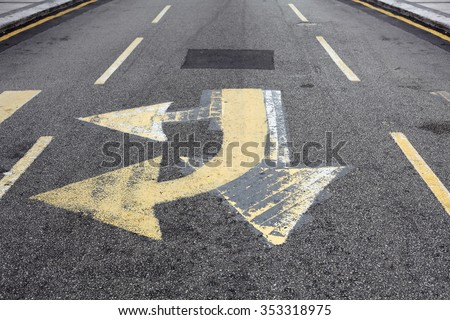 A faded multi directional arrow symbol on a city road for the concept of confusion  and indecisiveness. - stock photo