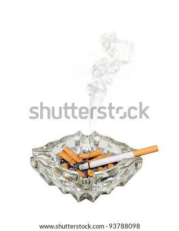 A fag burns shorter in a glass ashtray - stock photo