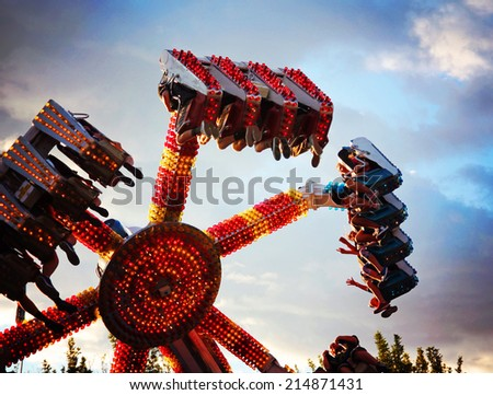 a fair ride during dusk on a warm summer evening - stock photo