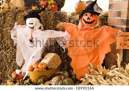 A fall display of ghosts, pumpkins, hay and fall leaves - stock photo