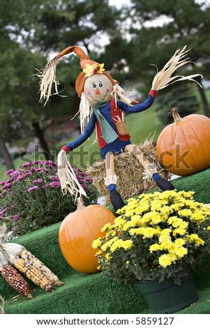 A fall display of pumpkins, straw, scarecrow and mums. - stock photo