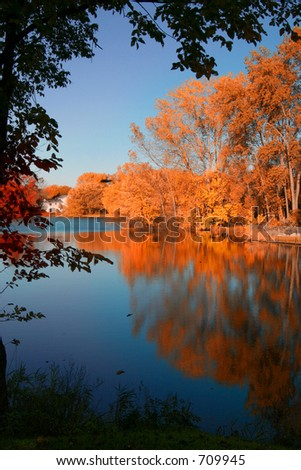 A fall lake scene like in a picture book. A lonely house overlooking a lake that is swarming with reflections of fall foliage. - stock photo