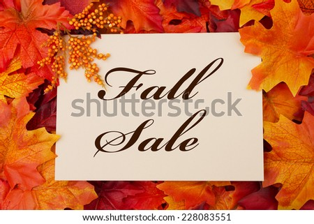 A Fall Sale card, A beige card with words Fall Sale over red and orange maple leaf background - stock photo