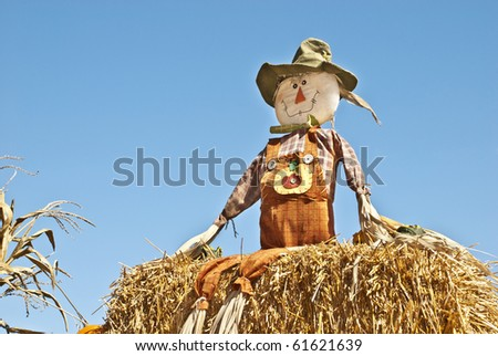 A fall scarecrow sitting on a bail of hay with blue sky background, copy space - stock photo