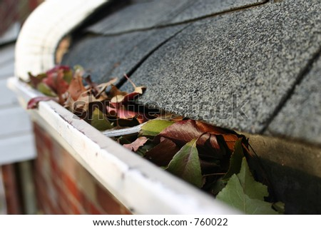 A fall tradition - cleaning the gutters of leaves. Here, we see them clogging the gutters of a traditional home. Could be used for advertising/clean up articles/etc. - stock photo