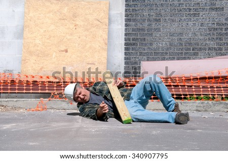 A fallen and injured construction worker in a hard hat laying on the ground at a construction work site - stock photo