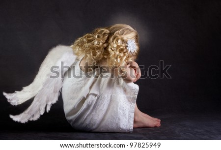 A fallen angel or child angel who is sad - stock photo