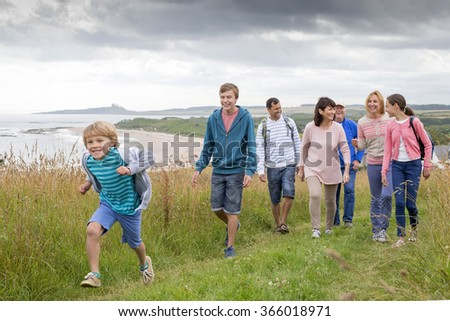 A family are walking on the sand dunes, they are all smiling and talking amongst themselves. - stock photo