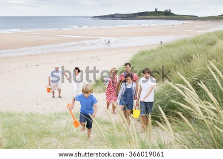 A family are walking up the sand dunes, leaving the beach. They are all smiling and talking with each other. - stock photo
