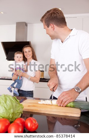 A family at home in the kitchen making a meal together, shallow depth of field, critical focus on father - stock photo
