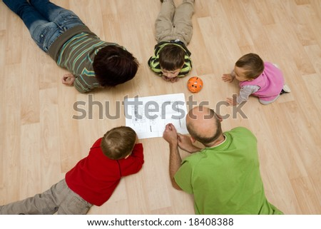 A family comprising parents and their 3 kids lying on the floor and checking the design of their new house on the paper. - stock photo