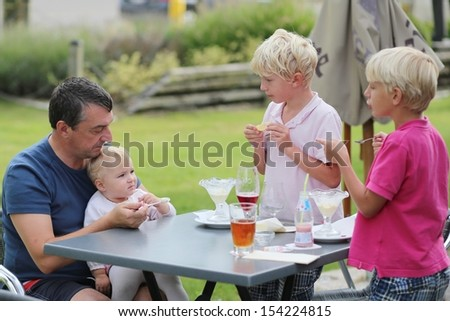 A family, father with two teenager sons and cute baby daughter are relaxing together outdoors in cafe on summer terrace eating ice cream and drinking beer and ice tea - stock photo