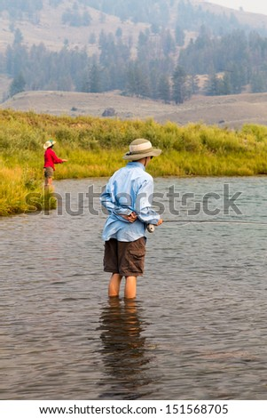 A family fishing in Yellowstone National Park at Slough Creek with fly rods and reels.  Smoke is in the air from forest fires in the region. - stock photo