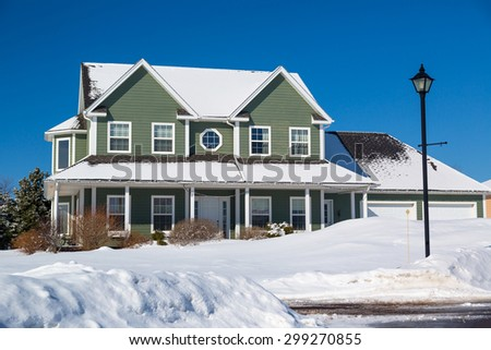 A family home in a north American suburb covered in snow. - stock photo