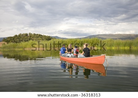 A family in a canoe on the pond. - stock photo