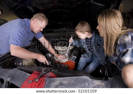A family in a garage working together and helping restore a car by using wrenches.