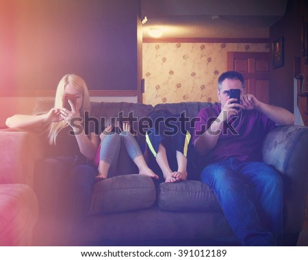 A family is together sitting on a couch with technology tablets in front of their faces for an entertainment or generation concept. - stock photo