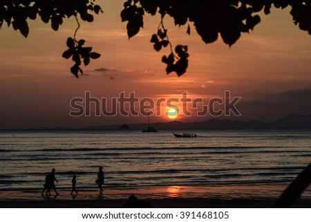 A family is walking by the beach during a beautifully orange-colored sunset in Ao Nang, Thailand. - stock photo