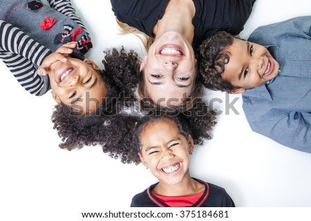 A family lay on the floor of a photography studio - stock photo