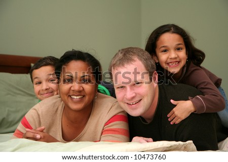 A family laying together on a large bed - stock photo