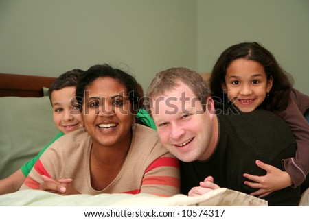 A family laying together on a large bed