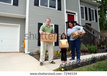 A family moves boxes into a new house - stock photo
