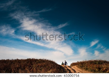 A family of a man, woman and son walking. - stock photo