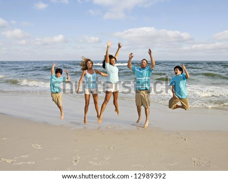 A family of five jumping on the Alabama Gulf Coast. - stock photo