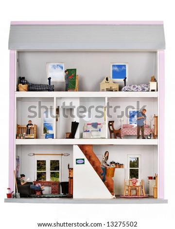 A family of five working and playing inside a furnished doll house. - stock photo