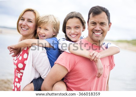 A family of four are at the beach together, the children are on their parents backs. They are all smiling looking at the camera. - stock photo